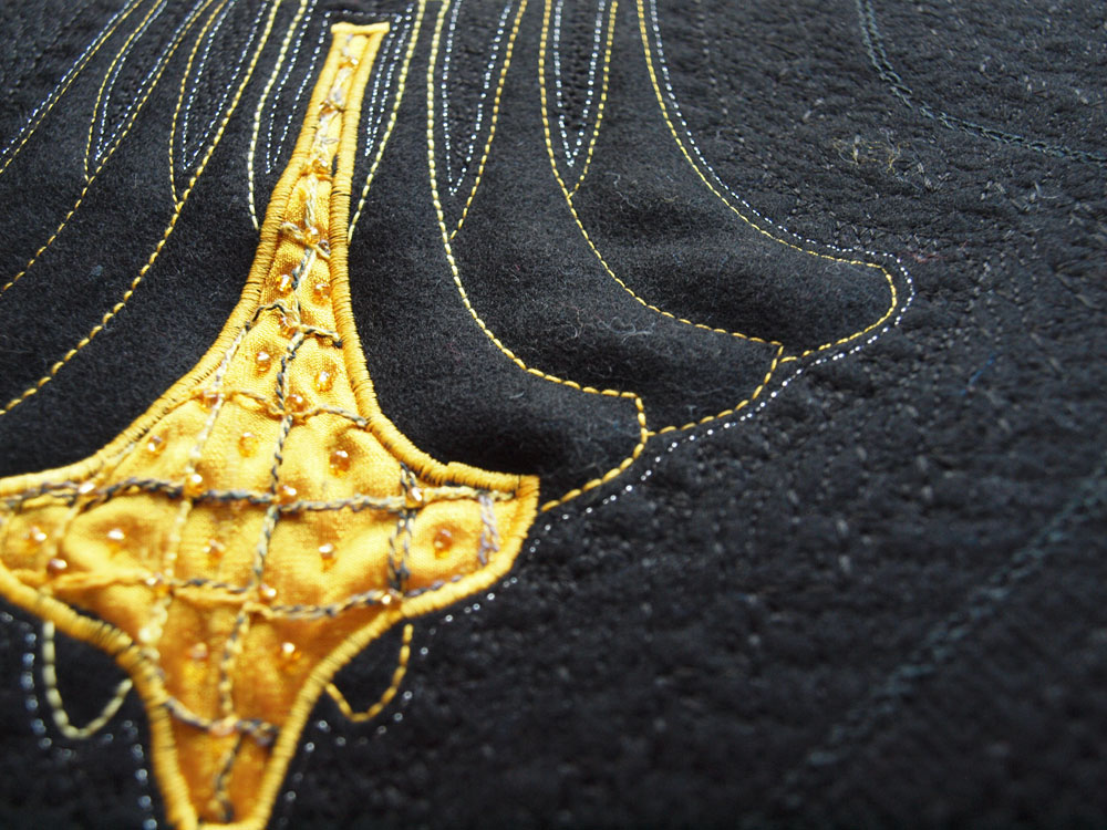 Close up detail of the embroidered detail on a hand sewn muff by textiles artist, Greta Huseboe
