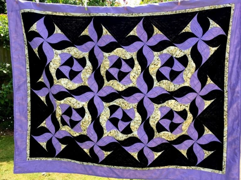 A purple and black abstract patchwork quilt