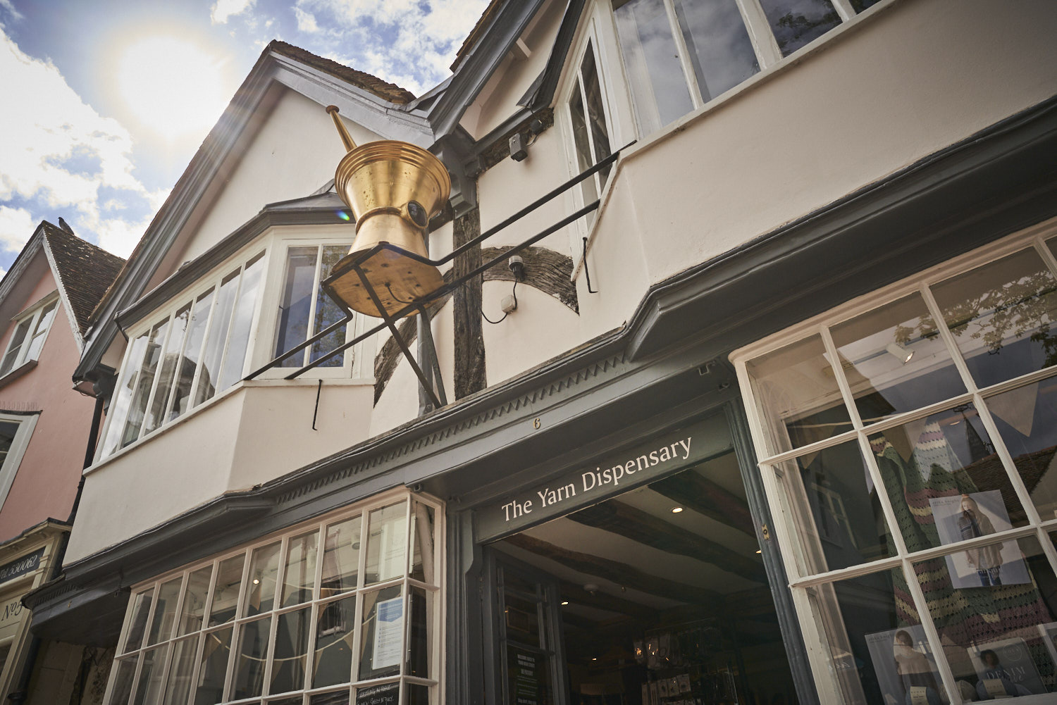 Image shows our iconic pestle and mortar, beamed ceilings inside the shop, and large bay windows in the apartment above.